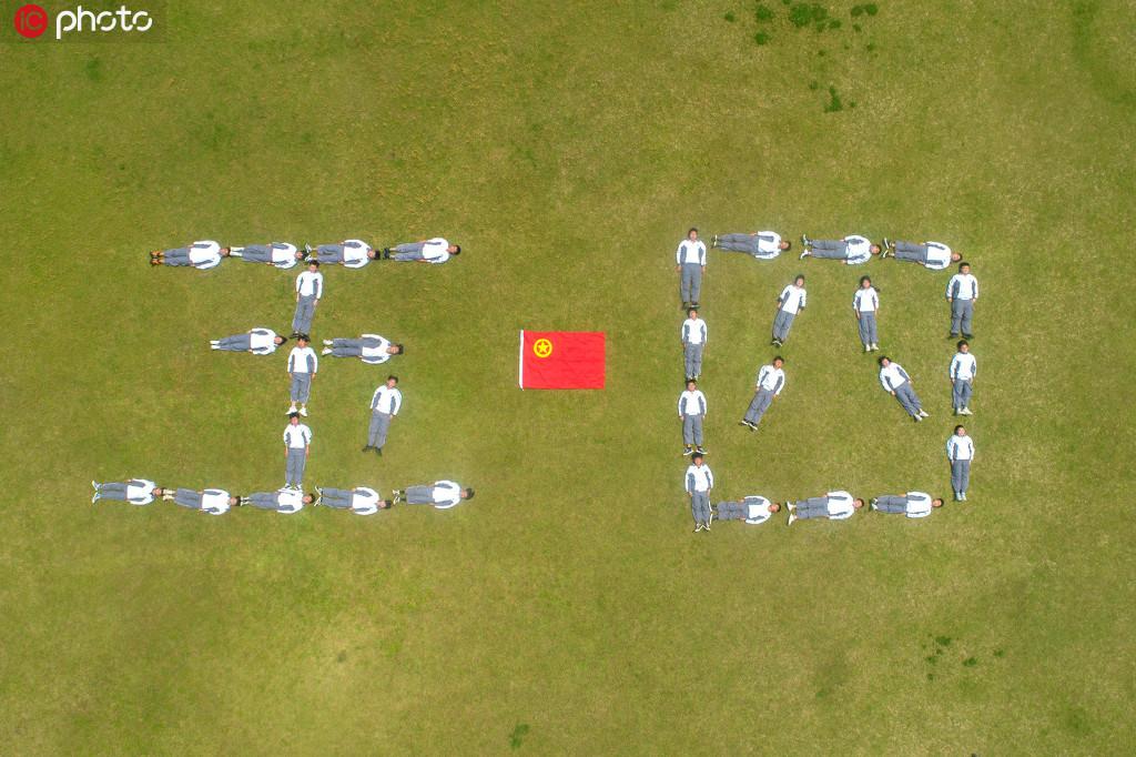 """2020年5月2日,浙江省湖州市長興職教中心,青年學生在操場上擺出""""五四""""造型,與團旗合影。(無人機航拍)"""
