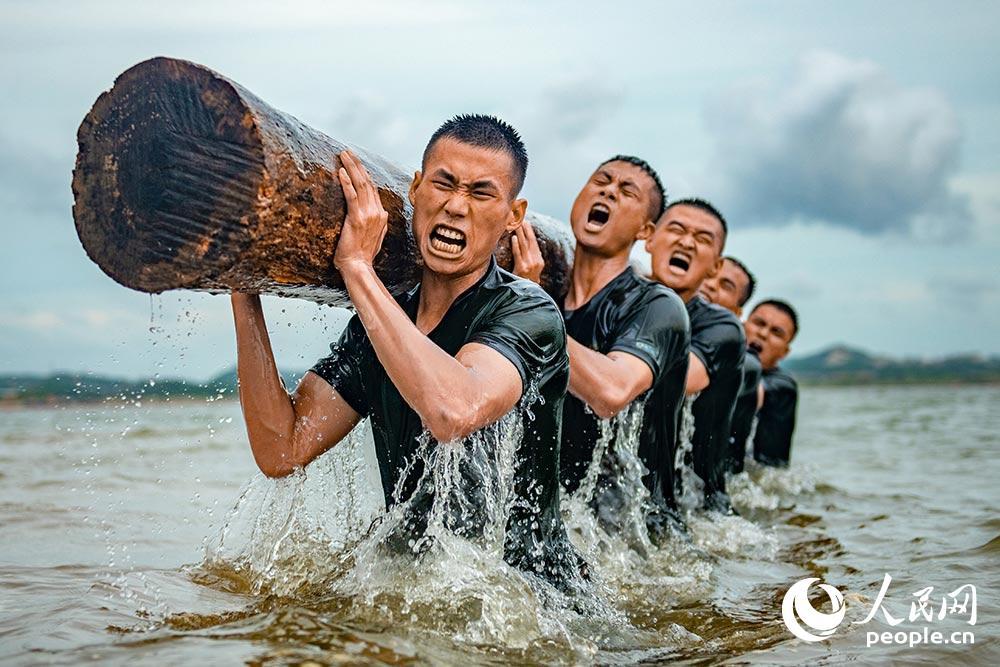 6月16日,武警官兵在海水中進行推舉圓木訓練。